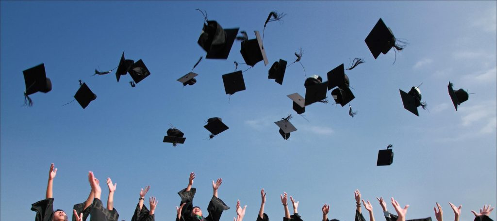 Graduation students throw their hats in the air